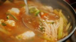 Pour hot soup from seafood ladle. Authentic Korean cuisine