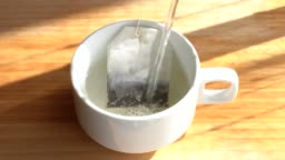 Pour hot water into a white cup with black tea sachets.