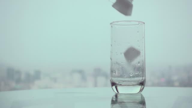 vidéos et rushes de verser la glace verre lent - glaçon