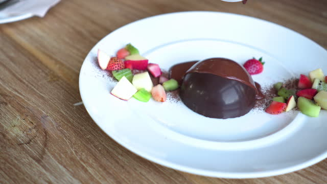 pour molten chocolate lava into molten chocolate cake, lava cake, with fruit, strawberry, kiwi, apple. valentine's day dessert on wood table. - serving size stock videos & royalty-free footage