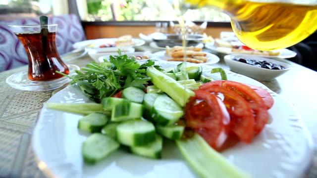 Häll olivolja över tomaterna på turkiska frukostbordet