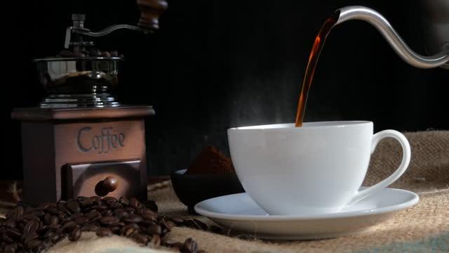 コーヒーをやかんからカップに注ぎます。 - 麻袋点の映像素材/bロール