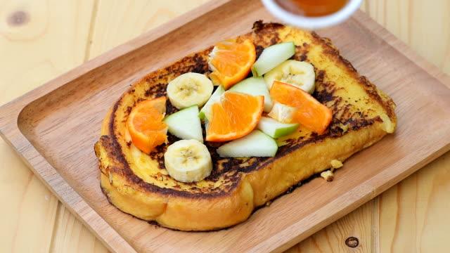 vídeos de stock, filmes e b-roll de despeje a calda de maple na rabanada com banana, maçã e laranja - ácer