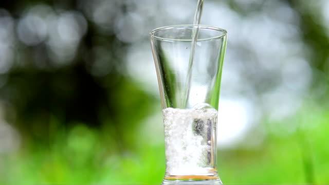 vídeos de stock e filmes b-roll de verter a água no copo - copo vazio