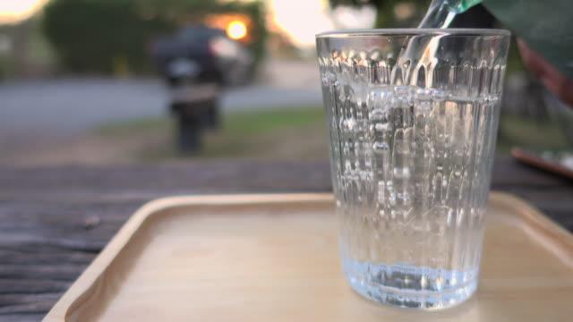 gießen sie wasser mit eis in glas sliding shot - wasserflasche stock-videos und b-roll-filmmaterial