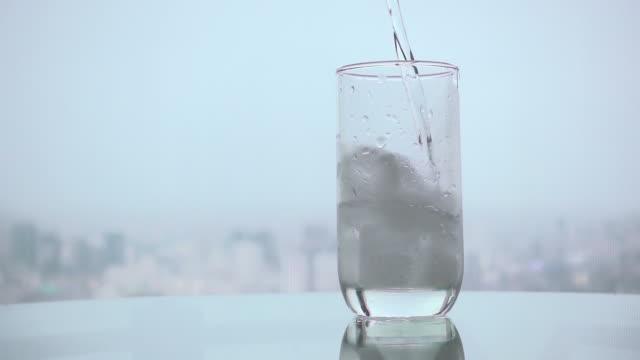 vídeos de stock, filmes e b-roll de despeje a água com gelo lento - congelado