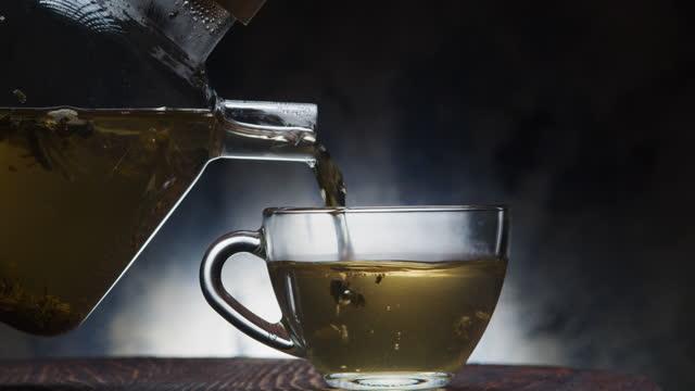 vídeos de stock, filmes e b-roll de derramando uma xícara de chá verde natural - vinheta