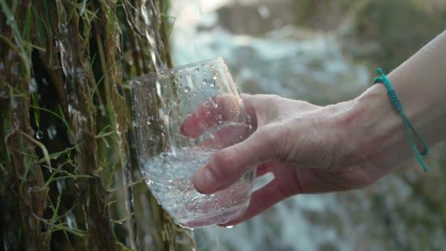 vidéos et rushes de versant un verre de l'eau cristalline de montagne - torrent