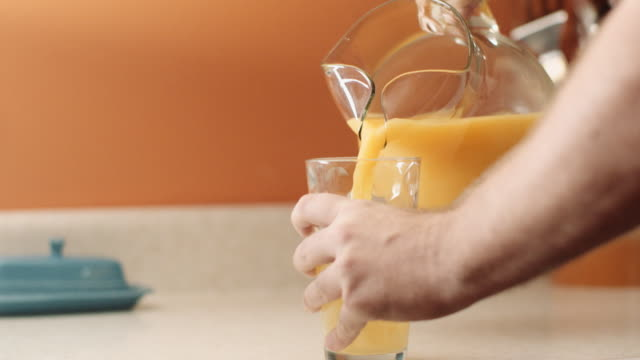 pouring a glass of orange juice - jug stock videos & royalty-free footage