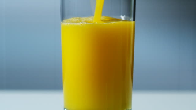pouring a glass of orange juice
