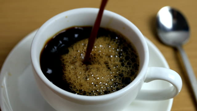 pouring a hot black coffee in to white cup on the table. - cup stock videos & royalty-free footage