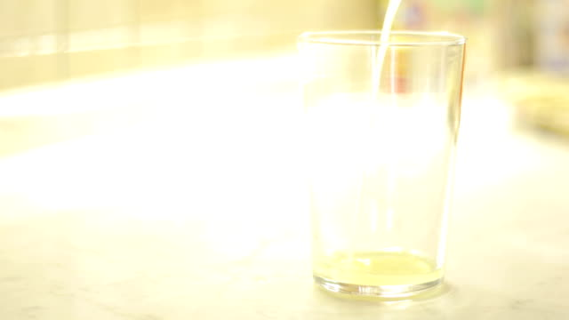 Pouring a Lemonade Nectar into Drinking Glass