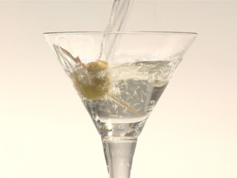 pouring a martini into a glass with a spanish olive - martini stock videos & royalty-free footage