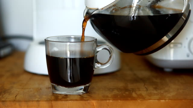 pouring a mug of hot coffee from a glass pot in the morning at home. - bricco per il caffè video stock e b–roll