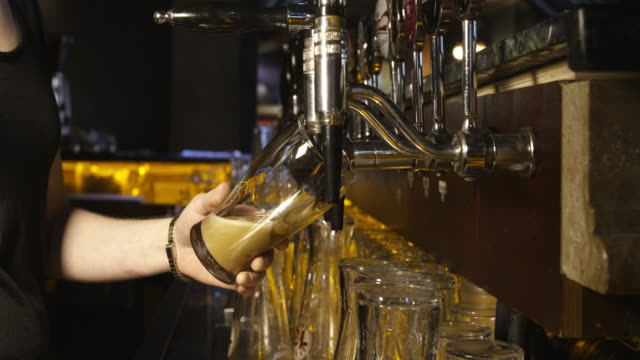 pouring a pint of guinness from beer tap in pub