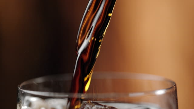 slo mo pouring a soft drink into a glass - carbonated drink stock videos & royalty-free footage