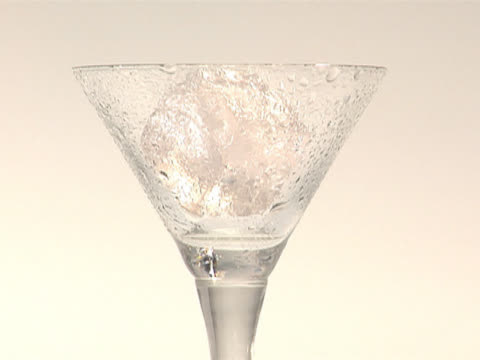 pouring alcohol into a martini glass with ice - martini glass stock videos and b-roll footage