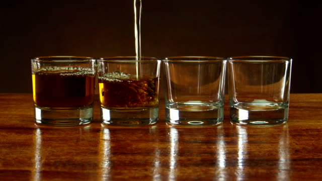 stockvideo's en b-roll-footage met pouring alcohol into four shot glasses on bar top - studio shot