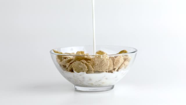 pouring almond milk on corn flakes for healthy diet breakfast - dairy product stock videos & royalty-free footage