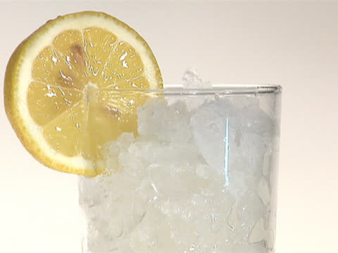 pouring apple juice into a glass with crushed ice and lemon, close up - crushed ice stock videos & royalty-free footage