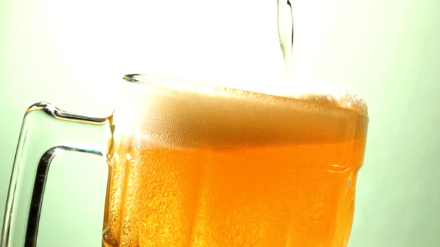 4k pouring beer in to beer glass - lager stock videos & royalty-free footage