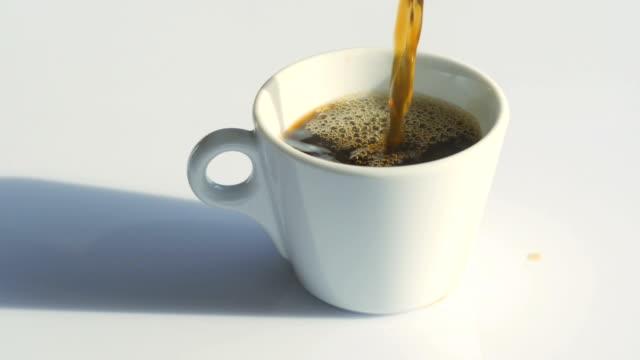 vidéos et rushes de verser le café noir dans une tasse avec de la vapeur naturelle et des bulles sur elle - tasse