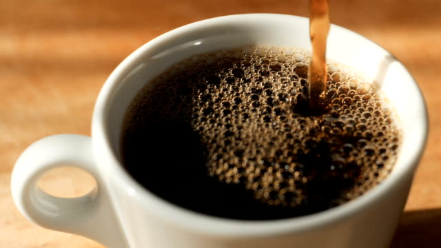pouring black coffee to a cup with natural steam and bubbles on it - bricco per il caffè video stock e b–roll