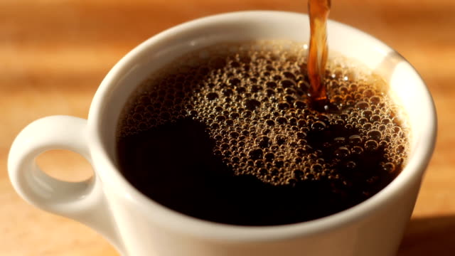 pouring black coffee to a cup with natural steam and bubbles on it - full stock videos & royalty-free footage