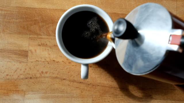 vídeos de stock, filmes e b-roll de dolly: café preto de derramamento a um copo com vapor natural nele - xícara de café