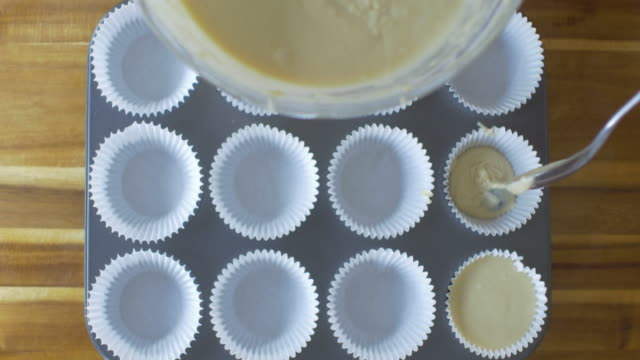 pouring blueberry muffin batter into cup tin - table top view stock videos & royalty-free footage