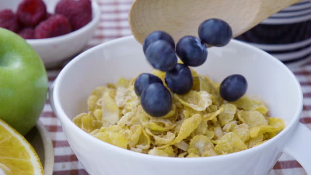 pouring blueberry on cornflakes cup slow motion. - blueberry stock videos and b-roll footage