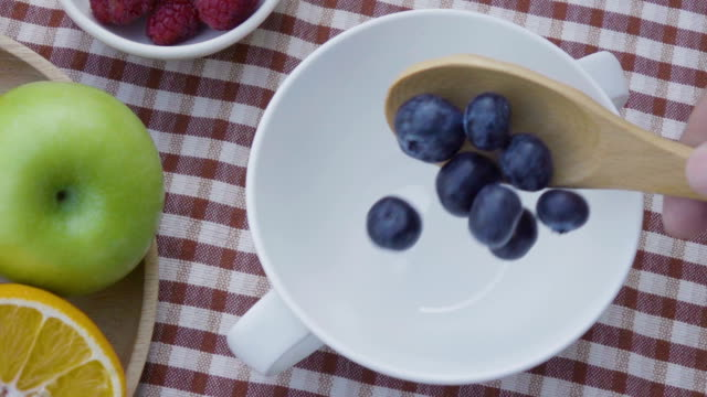 pouring blueberry on white cup slow motion. - blueberry stock videos and b-roll footage