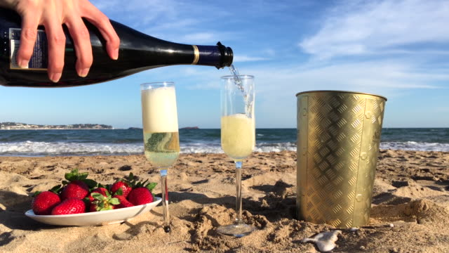 Pouring champagne on beach
