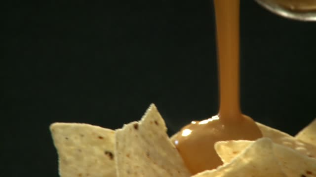 pouring cheese dip over tortilla chips - cheese stock videos & royalty-free footage