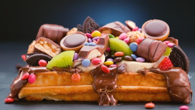 hälla choklad godis på toppad våffla med färska frukter, glass och vit choklad - slow motion - söt bildbanksvideor och videomaterial från bakom kulisserna