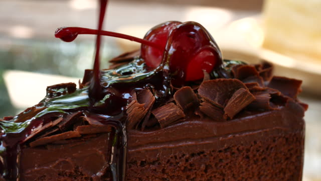 Pouring chocolate dressing over slice of cake