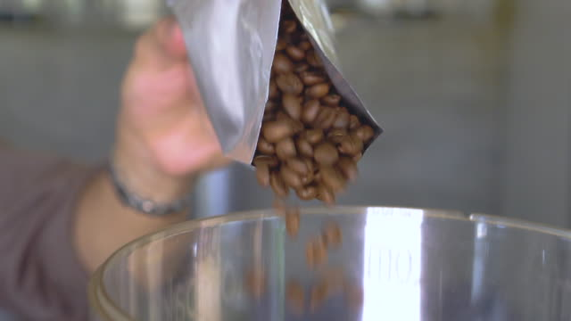 slomo pouring coffee beans from a bag - grinding stock videos & royalty-free footage