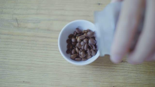 hälla kaffe bönor i liten kopp för griding