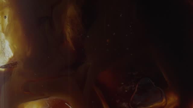 vídeos y material grabado en eventos de stock de pouring coffee into glass with ice water - marrón
