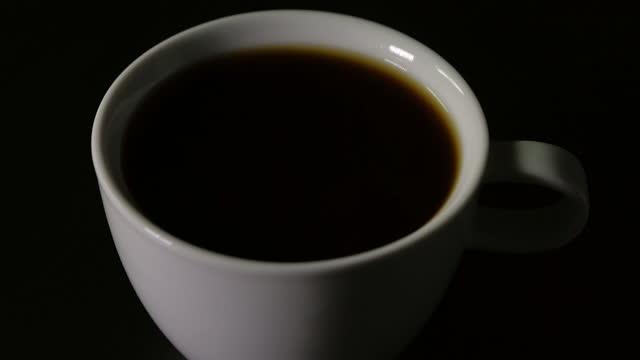 黒い背景を持つコーヒーを注ぐ - coffee cup点の映像素材/bロール