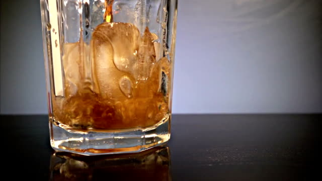 Pouring Cola Into Glass With Ice
