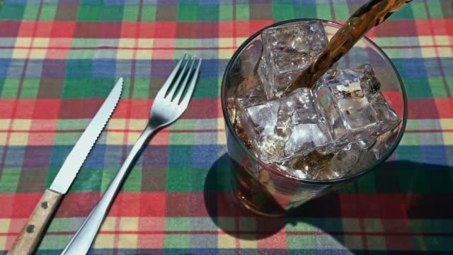 Gieten van cola soda in een glas van ijs op een eettafel