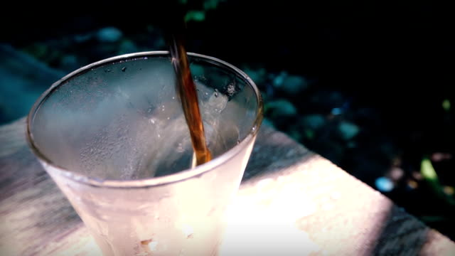 vídeos y material grabado en eventos de stock de el vertido de cola y de gaseosas en vaso de hielo con salpicaduras en movimiento lento - cola gaseosa