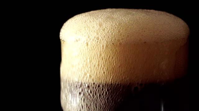 vídeos y material grabado en eventos de stock de verter la soda de cola en vaso de hielo con salpicaduras sobre fondo negro - cola gaseosa