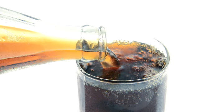 Pouring Cola with ice and bubbles in the glass. Close up soda soft drink. Food background isolated on white.