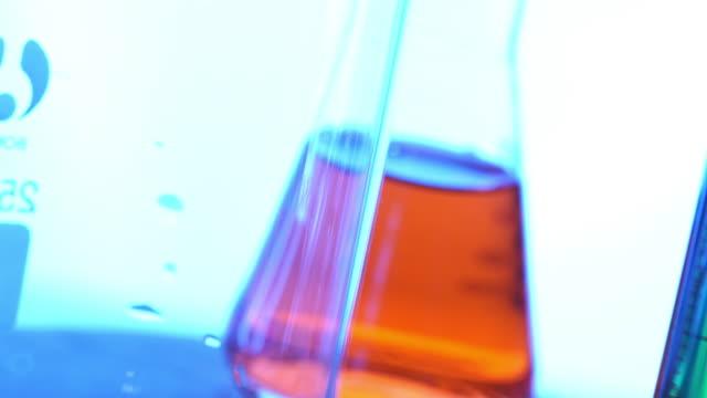 versare colore liquido in laboratorio grassware - pallone di vetro video stock e b–roll