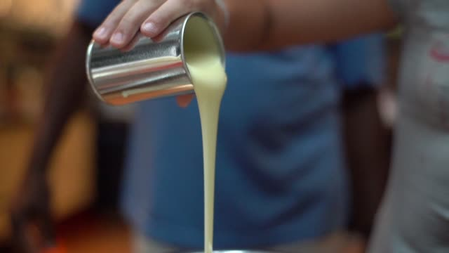 pouring condensed milk to preparing brazilian brigadeiro - jug stock videos & royalty-free footage