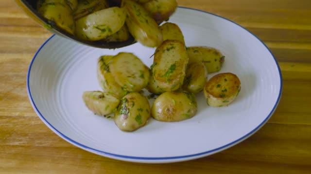 vidéos et rushes de verser de nouvelles pommes de terre cuites sur la plaque - pomme de terre