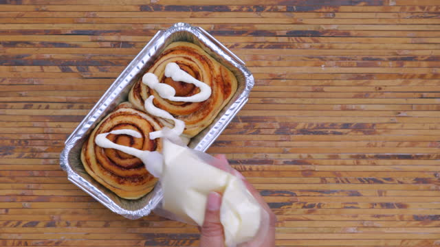 pouring cream cheese on cinnamon rolls top view - unhealthy eating stock videos & royalty-free footage