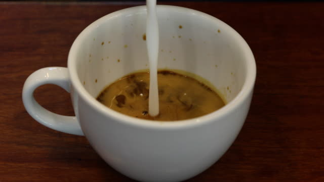 Pouring cream or milk into a cup of coffee.